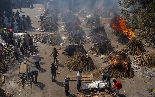 محارق جنائزية متعددة لضحايا كوفيد-19 في أرض تم تحويلها إلى محرقة جثث جماعية في نيودلهي، الهند، 24 أبريل 2021 (Altaf Qadri / AP)