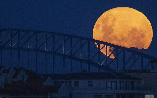 القمر يظهر فوق جسر ميناء سيدني في أستراليا، 27 أبريل 2021 (AP Photo/Mark Baker)