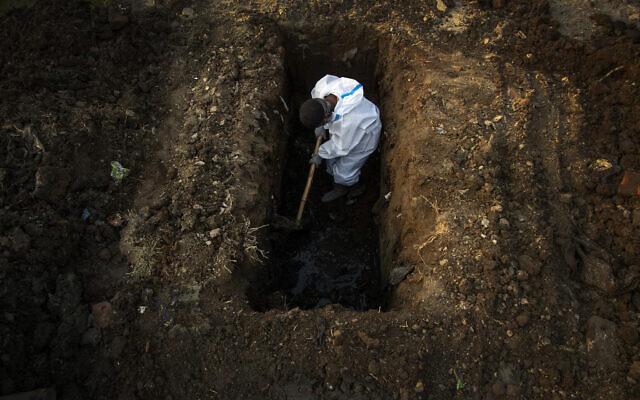 رجل يرتدي بدلة واقية يحفر الأرض لدفن جثة شخص توفي بعد إصابته بكوفيد-19 في جواهاتي، الهند، 25 أبريل 2021 (AP Photo / Anupam Nath ، File)