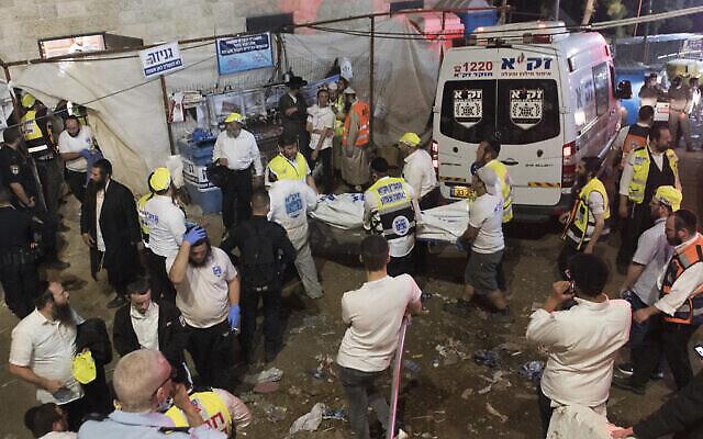 مسؤولون أمنيون وعمال إنقاذ إسرائيليون يحملون جثة أحد ضحايا التدافع خلال احتفالات لاغ باعمر في جبل ميرون في شمال إسرائيل، 30 أبريل، 2021. (AP Photo)