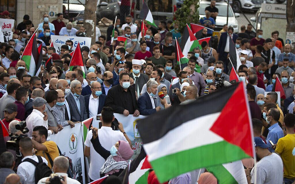 فلسطينيون يلوحون بالأعلام الفلسطينية خلال مظاهرة ضد تطبيع العلاقات بين الامارات والبحرين مع اسرائيل، في مدينة رام الله بالضفة الغربية، 15 سبتمبر، 2020. (Majdi Mohammed / AP)