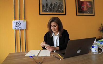 ديانا مقلد، صحفية لبنانية تتابع عن كثب وسائل التواصل الاجتماعي وتتفقد تطبيق Clubhouse، في مكتبها في بيروت، لبنان، 7 أبريل، 2021. (AP Photo / Hussein Malla)