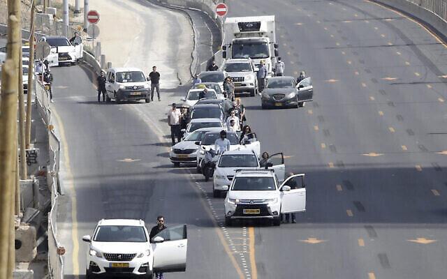 إسرائيليون يقفون بجانب سياراتهم مع إنطلاق صفارات الإنذار معلنة الوقوف دققتي صمت في جميع أنحاء البلاد لإحياء لذكرى 6 ملايين يهودي من ضحايا المحرقة، في تل أبيب، 8 أبريل، 2021. (AP Photo / Sebastian Scheiner)