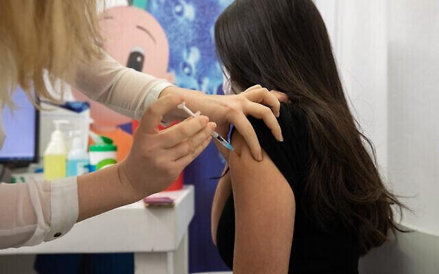 شابة اسرائيلية تتلقى حقنة لقاح كوفيد-19 في مركز تطعيم تابع لصندوق المرضى كلاليت في حولون، 4 فبراير 2021 (Chen Leopold / Flash90)