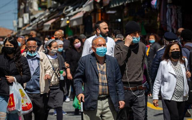 أشخاص يرتدون أقنعة وجه الثناء التسوق في سوق محانيه يهودا في القدس، 17 مارس 2021 (Olivier Fitoussi / Flash90)