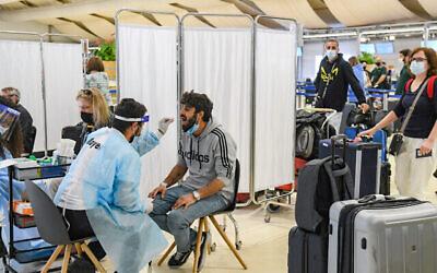فنيون طبيون يجرون اختبارات كورونا لمسافرين  في مطار بن غوريون الدولي بالقرب من تل أبيب، 8 مارس، 2021. (Flash90)