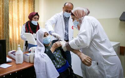 مسعفون فلسطينيون يتلقون لقاحا ضد فيروس كورونا في مركز طبي في مدينة دورا بالضفة الغربية، 21 مارس 2021 (Wisam Hashlamoun / FLASH90)
