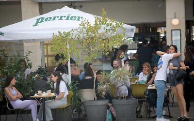 إسرائيليون في مقهى في تل أبيب، 7 أبريل، 2021. (Miriam Alster / FLASH90)