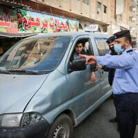 عناصر من الأمن الفلسطيني يجرون عمليات تفتيش في الشارع بعد أوامر بإغلاق قطاع غزة حتى 11 أبريل 2021 للحد من انتشار فيروس كورونا. (Abed Rahim Khatib/Flash90)