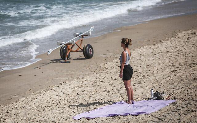 امرأة تقف دقيقتي على الشاطئ في تل أبيب ، مع إنطلاق صفارات الإنذار في جميع أنحاء إسرائيل لمدة دقيقتين بمناسبة اليوم السنوي لإحياء ذكرى ستة ملايين يهودي من ضحايا المحرقة النازية. (Miriam Alster / Flash90)