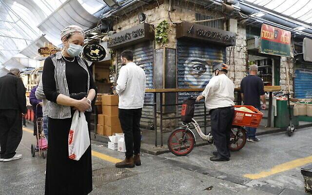 أشخاص يقفون دقيقتي صمت في القدس في 8 أبريل 2021 مع إطلاق صفارات الإنذار في جميع أنحاء إسرائيل لمدة دقيقتين بمناسبة اليوم السنوي لإحياء ذكرى ستة ملايين يهودي من ضحايا المحرقة النازية.  (Olivier Fitoussi/Flash90)