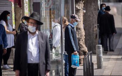 أشخاص يقفون دقيقتي صمت في القدس في 8 أبريل 2021 مع إطلاق صفارات الإنذار في جميع أنحاء إسرائيل لمدة دقيقتين بمناسبة اليوم السنوي لإحياء ذكرى ستة ملايين يهودي من ضحايا المحرقة النازية. (Yonatan Sindel / Flash90)