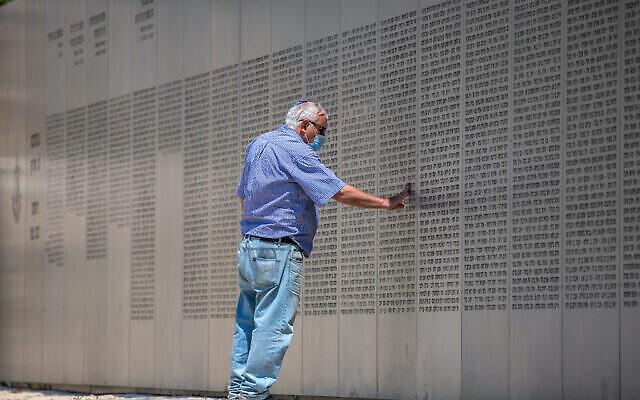 رجل إسرائيلي ينظر إلى جدار عليه أسماء الجنود القتلى من سلاح المدرعات في النصب التذكاري العسكري في اللطرون، 13 أبريل، 2021، قبل ساعات من انطلاق فعاليات يوم الذكرى الإسرائيلي الذي يبدأ هذا المساء. (Yossi Aloni / Flash90)