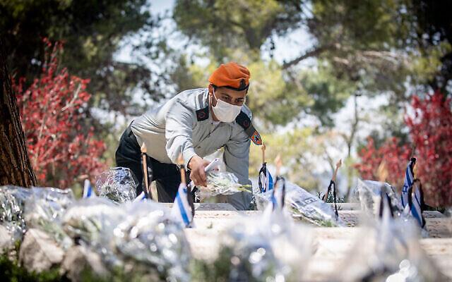 جنود إسرائيليون يزورون قبور  جنود من قتلى الحروب في مقبرة جبل هرتسل العسكرية في القدس، في 13 أبريل 2021، قبل ساعات من انطلاق فعاليات يوم الذكرى الإسرائيلي الذي يبدأ هذا المساء. (Yonatan Sindel / Flash90)