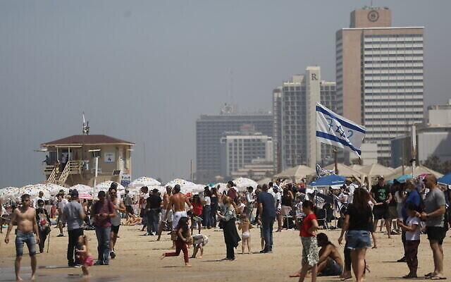 الإسرائيليون يستمتعون بالعرض الجوي بمناسبة يوم الاستقلال على شاطئ في تل أبيب، 15 أبريل، 2021. (Miriam Alster / Flash90)