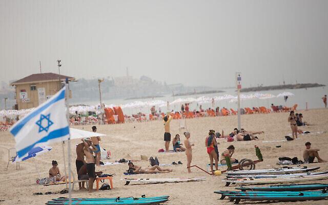 مستجمون إسرائيليون على أحد شواطئ تل أبيب في يوم ربيعي حار، ، 19 أبريل، 2021. (Miriam Alster / FLASH90)