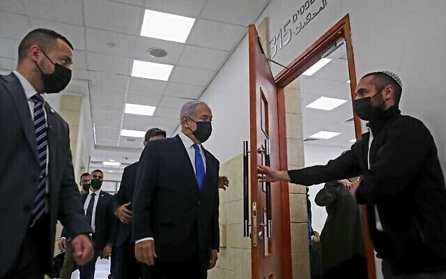 رئيس الوزراء بنيامين نتنياهو (وسط) يدخل قاعة محكمة القدس المركزية لجلسة استماع في محاكمته بالفساد، 5 أبريل 2021 (Oren Ben Hakoon / Pool)