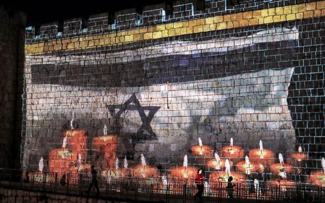"""صورة للعلم الإسرائيلي يرفرف أمام شموع معروضة على أسوار المدينة القديمة في القدس، بينما تعلن إسرائيل عن يوم حداد وطني على ضحايا التدافع خلال عطلة """"لاغ بعومر"""" في جبل ميرون، 2 مايو 2021 (AHMAD GHARABLI / AFP)"""