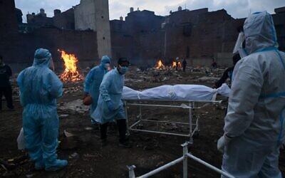 أقارب يرتدون بدلات ,واقية يحملون جثة شخص توفي جراء فيروس كورونا، في محرقة جثث في نيودلهي، 6 مايو 2021 (Prakash SINGH / AFP)