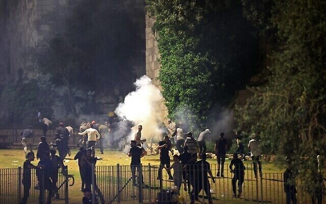متظاهرون فلسطينيون يهربون من الغاز المسيل للدموع الذي أطلقته قوات الأمن الإسرائيلية في البلدة القديمة بالقدس، 8 مايو 2021 (EMMANUEL DUNAND / AFP)