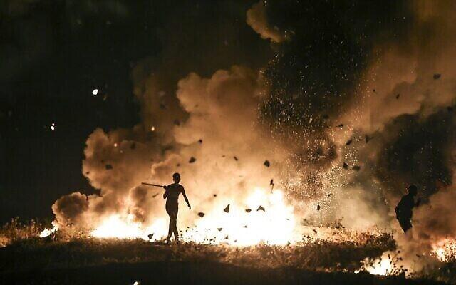 متظاهرون فلسطينيون يحرقون الإطارات خلال مظاهرة على الحدود بين إسرائيل وغزة، شرقي مدينة غزة، 8 مايو 2021 (MAHMUD HAMS / AFP)