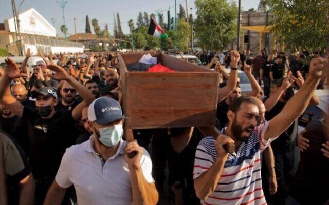 مواطنون عرب إسرائيليون يلوحون بالأعلام الفلسطينية أثناء تشييع جنازة موسى حسونة في مدينة اللد بوسط إسرائيل بالقرب من تل أبيب، في 11 مايو 2021. (AFP)