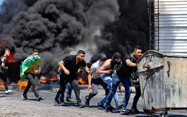 فلسطينيون يدفعون حاوية نفايات خلال مواجهات مع قوات الأمن الإسرائيلية بالقرب من حاجز حوارة جنوب مدينة نابلس بالضفة الغربية ،  14 مايو ، 2021 (Photo by JAAFAR ASHTIYEH / AFP)
