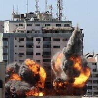 إنهيار البرج المؤلف من 13 طبقة والذي يضم مكاتب شركة الجزيرة ومكاتب وكالة اسوشيتد برس جراء ضربات صاروخية إسرائيلية 15 مايو 2021   (Photo by Mahmud Hams / AFP)