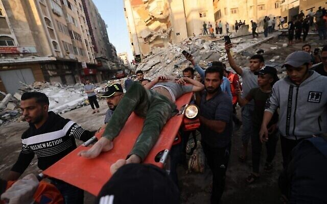 فلسطينيون يحملون أحد الناجين من تحت أنقاض أحد المباني بعد قصفه بغارات إسرائيلية في مدينة غزة، 16 مايو، 2021.