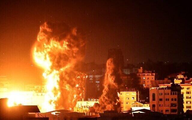 النار والدخان يتصاعدان فوق مبان في مدينة غزة فجر 17 مايو، 2021. ( Anas BABA / AFP)