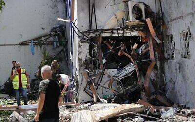 صور لسكان وفرق انقاذ اسرائيليين خارج مبنى اصيب بصاروخ اطلق من قطاع غزة في مدينة اشدود الجنوبية، 17 مايو، 2021. (Ahmad GHARABLI / AFP)