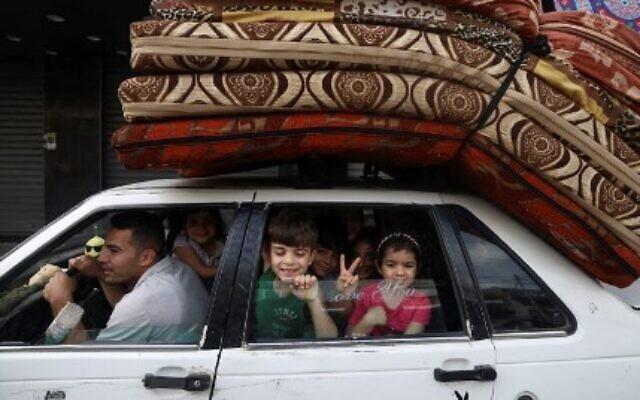مع سري مفعول وقف إطلاق النار، عائلة فلسطينية تعود الى منزلها بعد نزوحها مع بدء التصعيد بين إسرائيل وحركة حماس المسيطرة على قطاع غزة 21 مايو 2021 (Photo by MAHMUD HAMS / AFP)