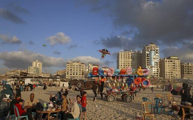 فلسطينيون يتجمعون على الشاطئ في مدينة غزة في 22 مايو 2021، بعد وقف إطلاق النار الذي أنهى 11 يوما من الضربات الجوية الإسرائيلية المستمرة على القطاع الساحلي الذي تديره حركة حماس.  (MAHMUD HAMS / AFP)