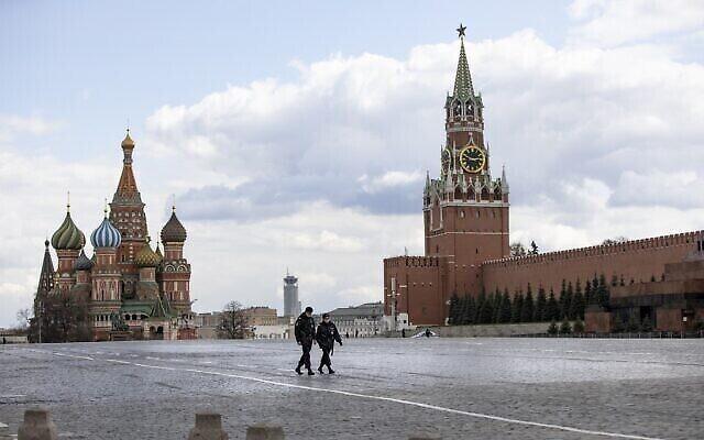 شرطيان يقومان بدورية في الساحة الحمراء شبه الخالية في موسكو، روسيا، 20 أبريل، 2020. (AP Photo / Alexander Zemlianichenko)
