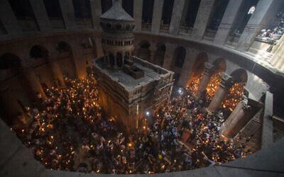 """حجاج مسيحيون يحملون الشموع أثناء تجمعهم خلال طقوس """"سبت النور"""" في كنيسة القيامة، موقع صلب ودفن وقيامة المسيح حسب المعتقدات المسيحية، في البلدة القديمة في القدس، يوم السبت، 1 مايو، 2021. (AP Photo / Ariel Schalit)"""