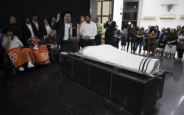 أفيغدور حايوت (يسار)، يجلس خلال جنازة نجله يديديا حايوت في مقبرة في بيتاح تكفا، 2 مايو 2021 (AP Photo / Sebastian Scheiner)