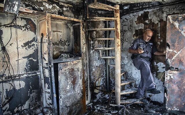 آفي كوركاس يفحص الأضرار التي لحقت بمكتب بلدية تم إحراقه في ليلة من أعمال العنف بين متظاهرين عرب إسرائيليين وشرطة إسرائيل في مدينة اللد، 11 مايو، 2021. (AP Photo / Heidi Levine)