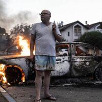 يعقوب سيمونا يقف بجانب سيارته المحترقة خلال اشتباكات بين عرب إسرائيليين والشرطة في اللد، إسرائيل، 11 مايو 2021 (AP Photo / Heidi Levine)