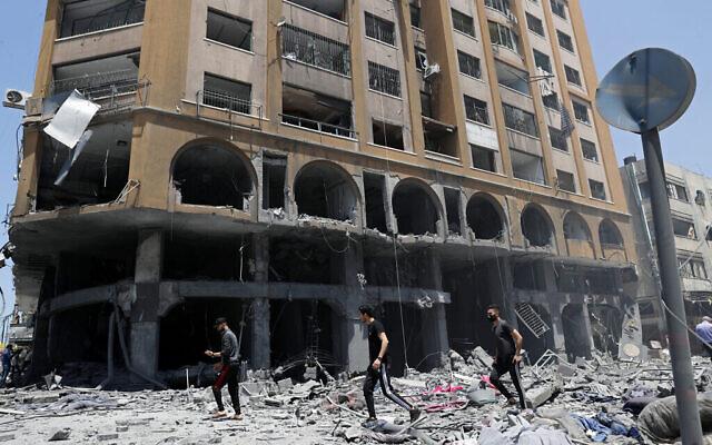 أشخاص يتفقدون أنقاض مبنى أصابته غارة جوية إسرائيلية بعد إطلاق صواريخ كثيف من القطاع، في مدينة غزة، 12 مايو 2021 (AP Photo / Adel Hana)