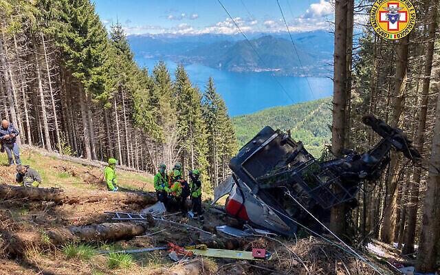 عمال الإنقاذ يعملون بالقرب من حطام تلفريك بعد سقوطه بالقرب من قمة خط ستريسا-موتاروني في منطقة بيدمونت ، شمال إيطاليا ، 23 مايو، 2022.   (Soccorso Alpino e Speleologico Piemontese via AP)