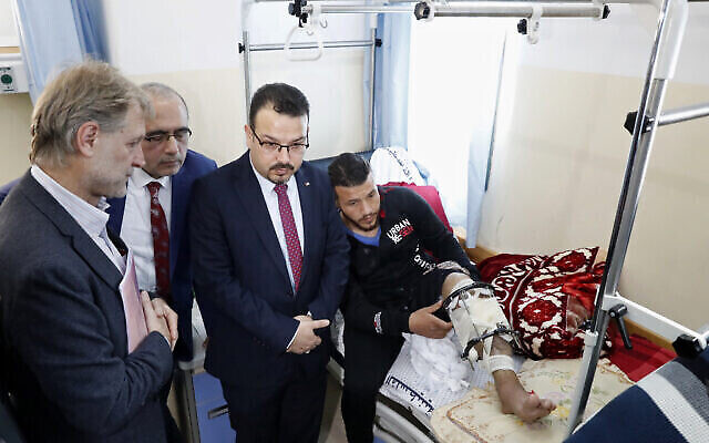 الدكتور جيرالد روكينشاب، مدير منظمة الصحة العالمية في الأراضي الفلسطينية (يسار) ، يستمع لأطباء فلسطينيين خلال جولة في مركز إعادة بناء الأطراف في مستشفى ناصر في مدينة خان يونس، جنوب قطاع غزة، 5 مارس، 2020. (Adel Hana/AP)