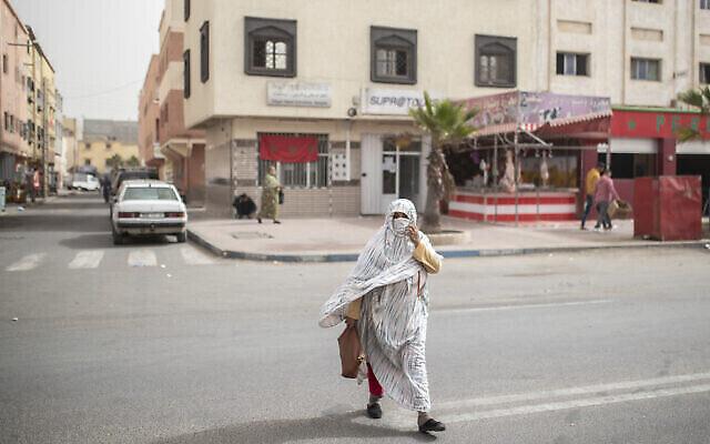 """سيدة ترتدي ملابس صحراوية تقليدية تعرف باسم """"ملحفة"""" تعبر طريقا في مدينة الداخلة، الصحراء الغربية، 21 ديسمبر، 2020. (AP Photo / Mosa'ab Elshamy)"""