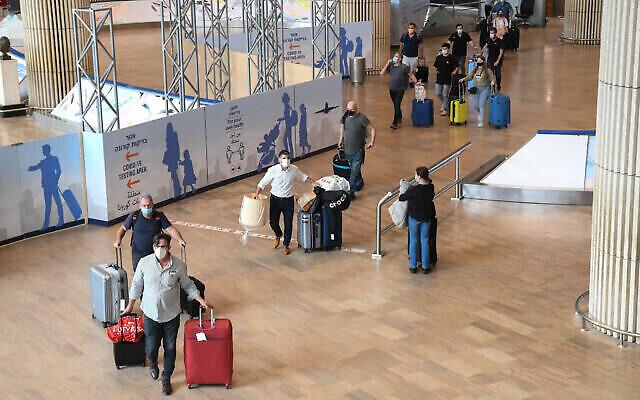 مسافرون يتوجهون إلى محطة اختبار فيروس كورونا بعد وصولهم إلى مطار بن غوريون في 8 مارس، 2021. (Flash90)