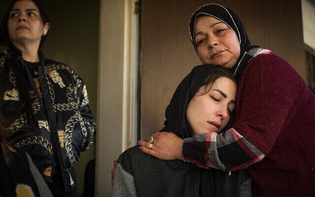 أفراد عائلة منير عنبتاوي البالغ من العمر 33 عاما، والذي قُتل رميا بالرصاص بعد محاولته كما يُزعم طعن ضابط شرطة، في منزلهم في حيفا، 30 مارس، 2021. (Roni Ofer / Flash90)