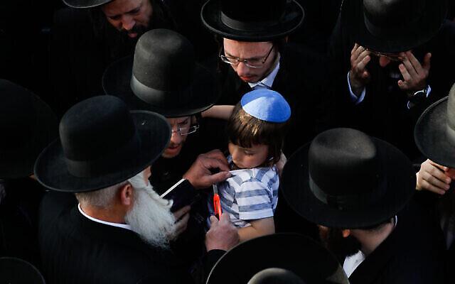 في علامة حداد لشخص فقد أحد أقربائه، يقوم رجل بقص قميص يوناتان، البالغ من العمر أربع سنوات، وهو نجل يهودا ليب روبين، الذي توفي في مأساة ميرون، 30 أبريل 2021 (Olivier Fitoussi / Flash90)