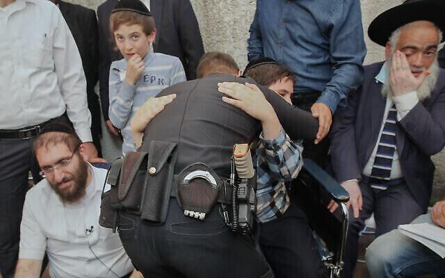 الشرطي رامي علوان يعانق شموئيل حايوت الذي أنقذه في ميرون. الأب أفيغدور حايوت يجلس إلى اليسار في منزل العائلة في بني براك، 3 مايو، 2021. (Flash90)
