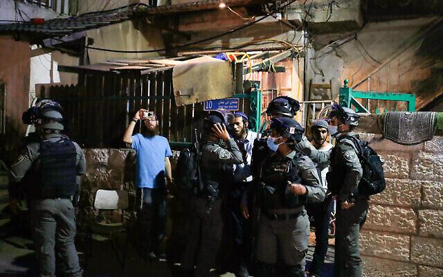 القوات الإسرائيلية تحرس خارج مبنى تعيش فيه عائلة يهودية خلال مظاهرة فلسطينية في حي الشيخ جراح بالقدس الشرقية، 4 مايو 2021 (Jamal Awad/FLASH90)