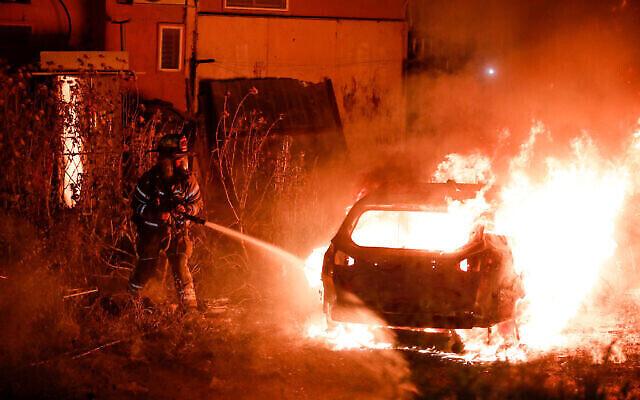 رجال إطفاء يخمدون سيارة تابعة لعائلة يهودية أضرمت فيها النيران في حي الشيخ جراح في القدس الشرقية، 6 مايو ، 2021 (Olivier Fitoussi / Flash90)