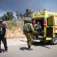 جنود إسرائيليون بالقرب من الموقع الذي أصيبت فيه مركبة اسرائيلية بصاروخ مضاد للدبابات أطلق من غزة، 12 مايو 2021 (Yonatan Sindel / Flash90)