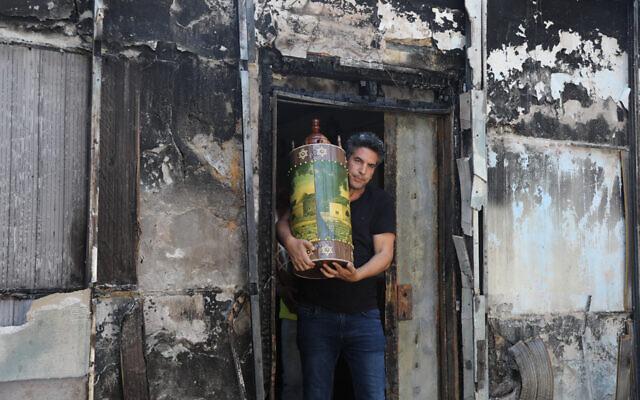 إسرائيليون يخرجون لفائف توراة من كنيس يهودي محترق في مدينة اللد وسط إسرائيل، بعد ليلة من أعمال الشغب العنيفة من قبل السكان العرب في المدينة، 12 مايو 2021 (Yonatan Sindel / Flash90)
